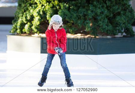 smiling positive boy enjoying ice skating at outdoor skating rink with christmas tree in the background winter holiday or vacation activity