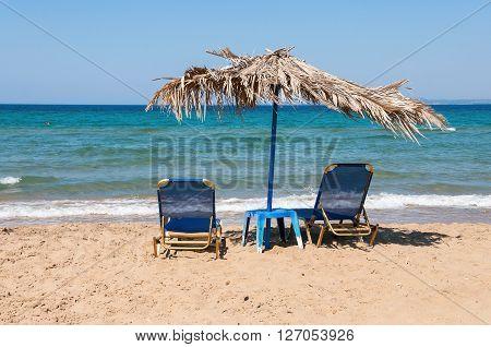 Sunbeds and straw umbrella on Banana beach Zakynthos Greece