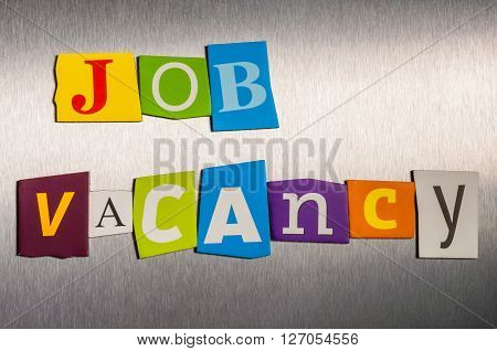 The word Jobs  Vacancy in color cut out magazine letters on metal background. Hiring concept.