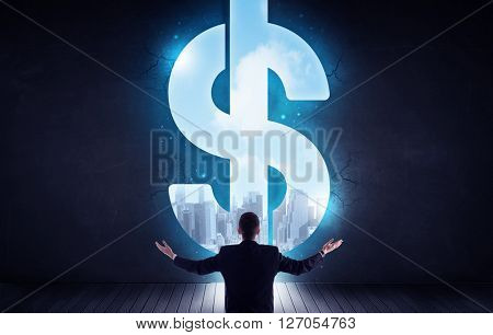Businessman looking at wall with hole in form of dollar