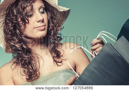 Stylish young woman love shop. Happy with new clothes Girl in green light dress and hat hold shopping bag.
