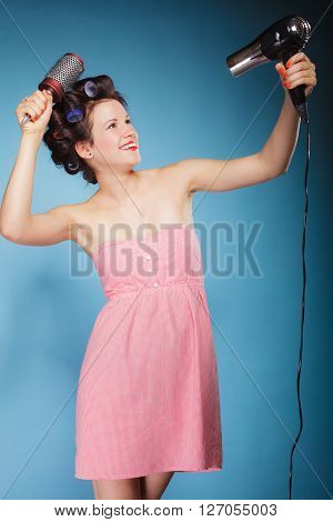 Young woman preparing to party having fun funny girl styling hair with curlers hairbrush and hairdreyer retro style blue background