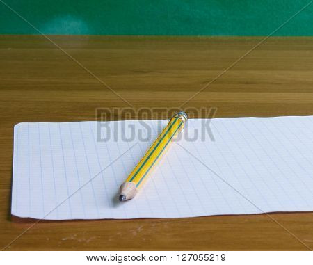 Page from the notebook with pencil lying on the desk