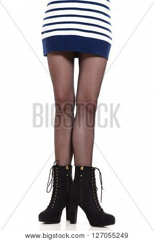 Beauty and fashion of female. Long slim attractive woman legs in tights and high heels boots. Part body girl in striped dress skirt isolated on white.
