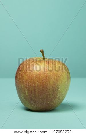 A single red cox apple on a blue green background lit from the left with a soft shadow to side