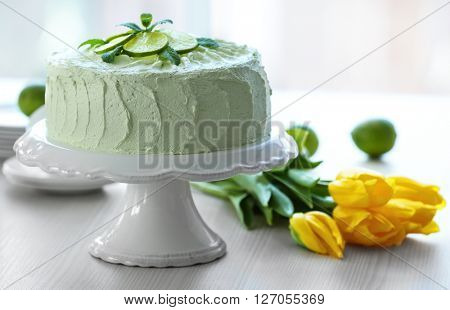 Big lime cake and bouquet of yellow tulips.