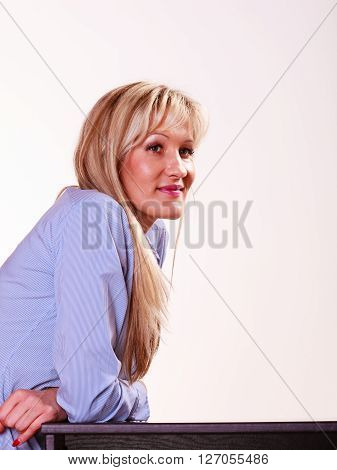 Relax free time waiting and thinking. Middle aged woman with long blond hair sit at table smiling.