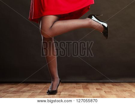 Woman part body. Dance posing girl in red dress on gray background in studio.
