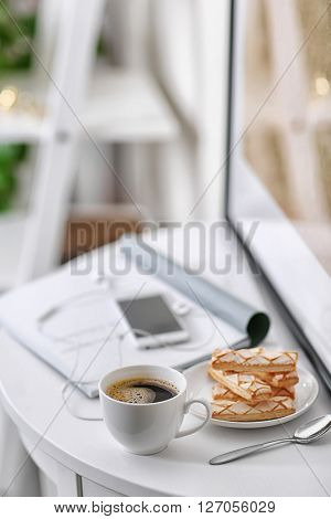 White cup of the coffee and a phone on the table  in a light room..