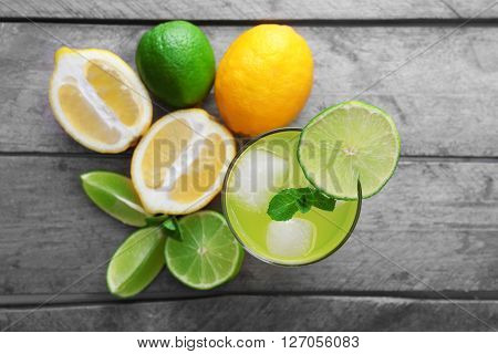 Glasses of lemon soda with ice and fresh mint on rustic wooden background