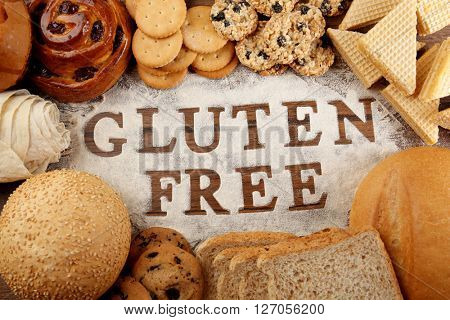 Text GLUTEN FREE with bakery products and flour on wooden surface closeup