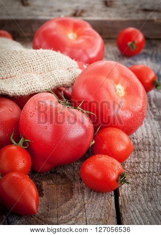 Fresh ripe tomatoes in a bag on wooden table