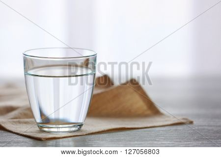 Glass of fresh water on wooden table