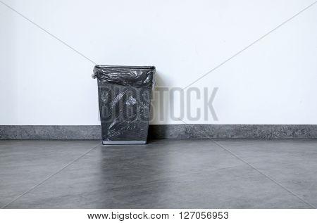 Empty rubbish basket on black floor and white wall behind. Photo-image