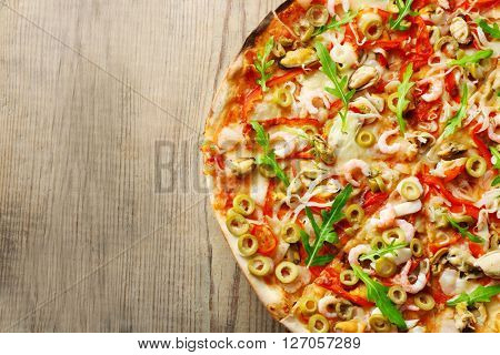 Pizza with seafood, red pepper and green olives on wooden table