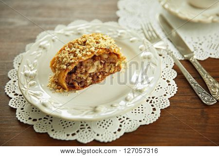 Slice of strudel with apples, walnut and raisins on white plate