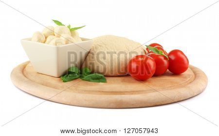 Fresh dough and other different ingredients for pizza on cutting board isolated on white
