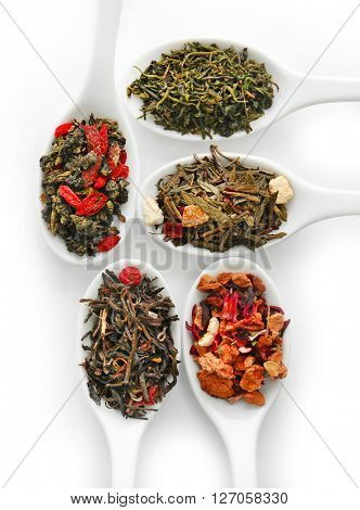 Different sorts of dry tea in ceramic spoons, isolated on white