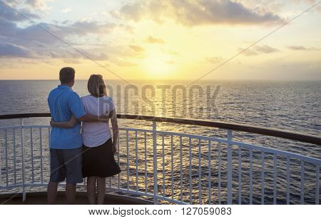 Couple on a cruise watching the sunset over the ocean