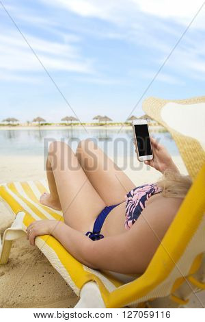 Woman on mobile phone at a tropical beach vacation. Relaxing in a chaise lounge chair