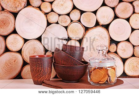 Utensil and glass jar with cookies on wooden background