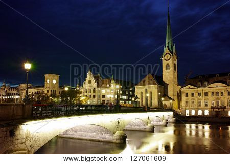 Night photo of Fraumunster Church and bridge over Limmat River, city of Zurich, Switzerland