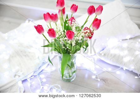 Red tulips in vase on the floor beside pillows