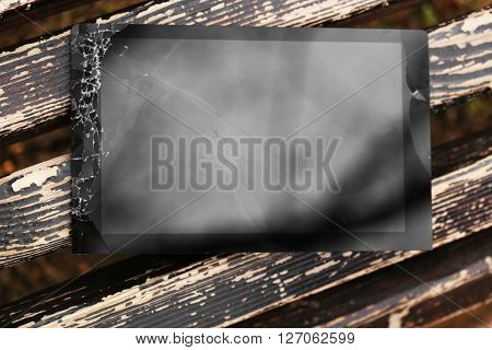 Broken tablet with cracked screen on wooden bench