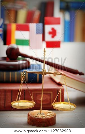 Justice scales with gavel and stack of books on wooden table