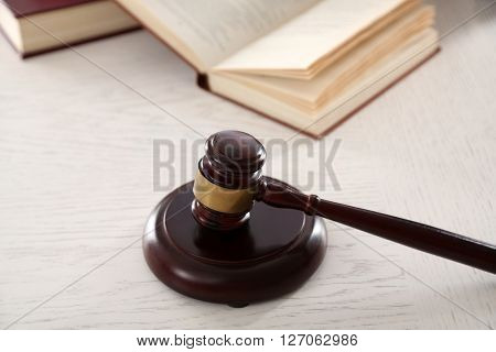 Gavel with books on wooden table closeup