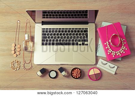 Laptop and female accessories on wooden table, top view