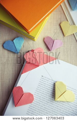 Books and heart shaped bookmarks on a light wooden background