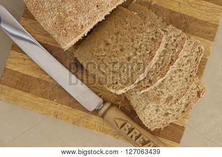 Loaf of sliced wholemeal bread with a knife.