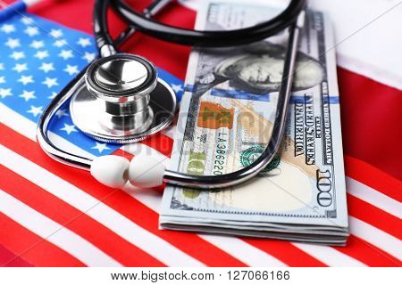Stethoscope with dollar banknotes on background of USA flag