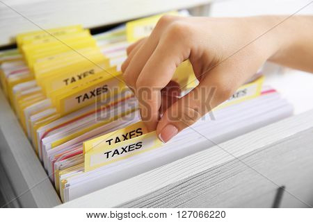 Hand searching through variety of tax documents in open drawer