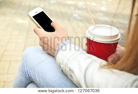 Woman sitting and use smartphone and drink coffee