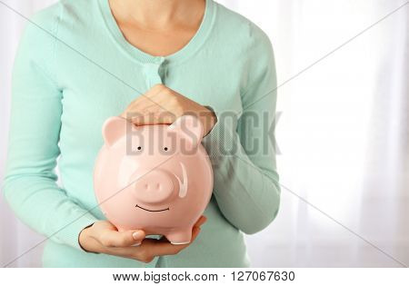 Woman holding piggy bank in hand. Financial savings concept