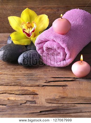 Spa still life with stones, flower and candlelight on wooden background