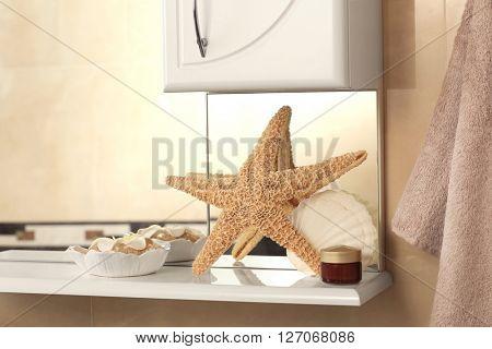 Starfish with shell and orange salt on a shelf in bathroom