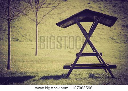Wooden table and bench on a green meadow, toned photo