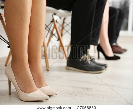 Legs of people sitting on chair, indoors