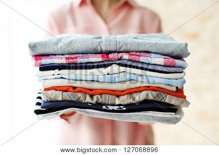 Woman holding clean male clothes, closeup