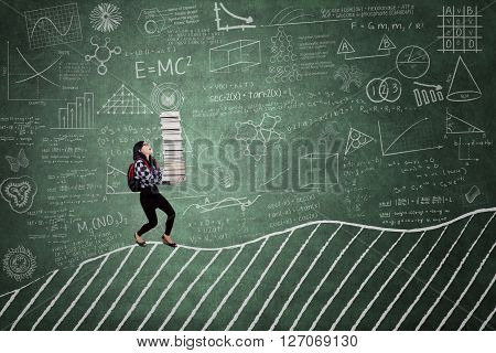 Image of a female college student bring a pile of book on the chalkboard in the classroom