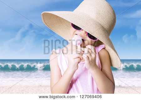 Portrait of little girl standing on the beach while wearing swimsuit and hat enjoying ice cream