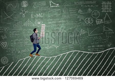 Picture of a male high school student carrying a stack of book on the chalkboard in the classroom
