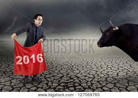 Young businessman holding a red flag with number 2016 to fight with a bull shot outdoors