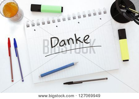 Danke - handwritten text in a notebook on a desk - 3d render illustration.