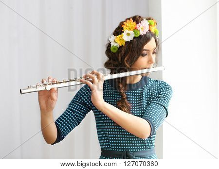 Beautiful young woman with flute on wall background