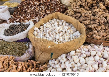 Garlic, ginger and spices in bags on a market in India