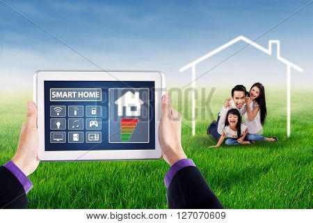Hands holding tablet with smart house technology system on the screen shot with cheerful family playing under a house symbol